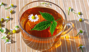 Cup of herbal tea with chamomile and green leaf still life