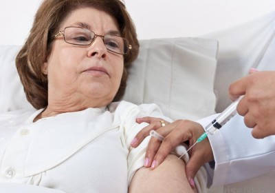 woman-in-glasses-receiving-injection-in-left-arm